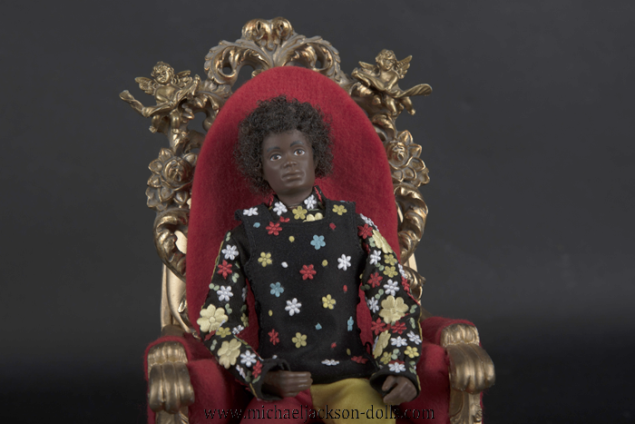 Michael Jackson doll as a child on red chair close up